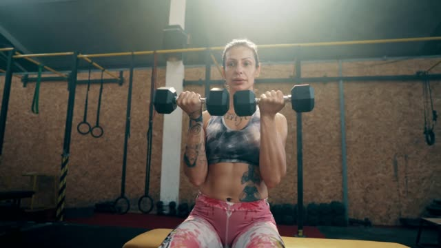 young woman working out with dumbbells - dumbbell stock videos & royalty-free footage