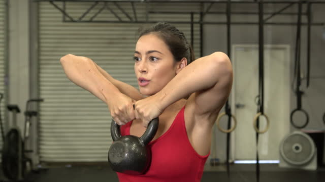 MS Young woman working out with kettlebells in a gym