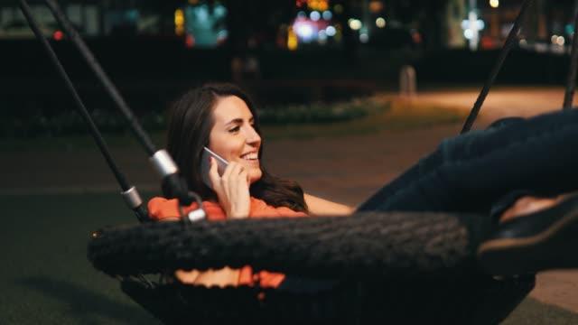 vídeos de stock, filmes e b-roll de trabalho da mulher nova ao ar livre na noite - swing