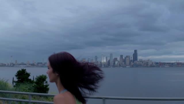 ung kvinna arbetande ute/klappa hund framför seattle skyline. - strandnära bildbanksvideor och videomaterial från bakom kulisserna