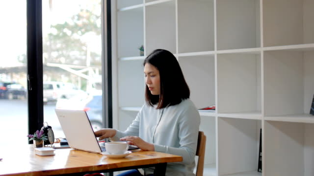 young woman working with laptop at library with hot coffee - large group of objects stock videos & royalty-free footage