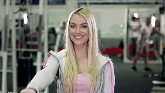 vidéos et rushes de jeune femme travaillant avec des haltères dans la salle de sport - poids pour la musculation