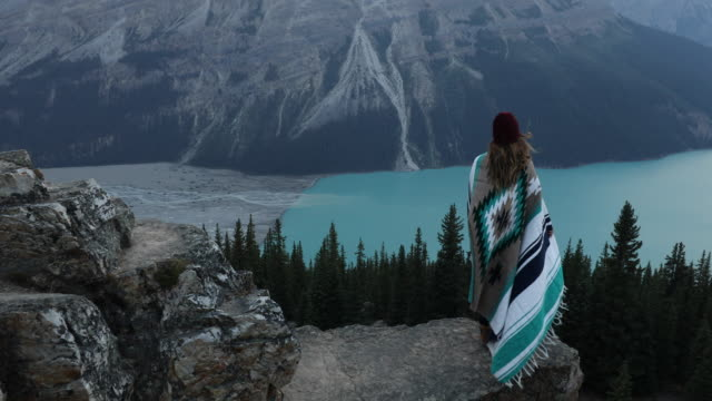 vídeos de stock e filmes b-roll de a young woman wrapped in a blanket overlooking peyto lake in banff - canadá