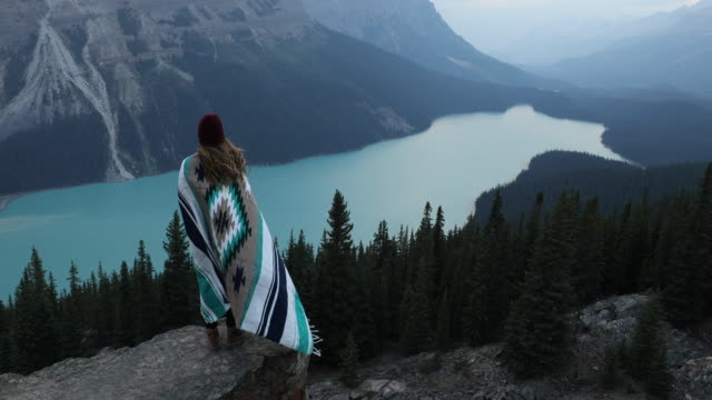 a young woman wrapped in a blanket overlooking peyto lake in banff - see stock-videos und b-roll-filmmaterial