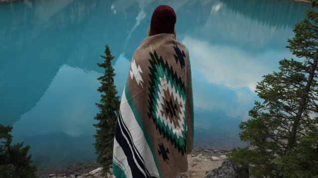 a young woman wrapped in a blanket taking in the scenic view over the turquoise waters of moraine lake. - banff national park stock videos & royalty-free footage