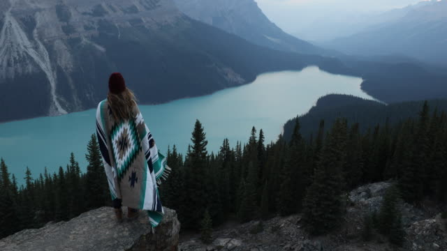 A young woman wrapped in a blanket watching sunrise over a lake.