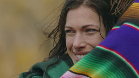 young woman wrapped in towel leans on man and smiles as she looks around. - wet hair stock videos & royalty-free footage