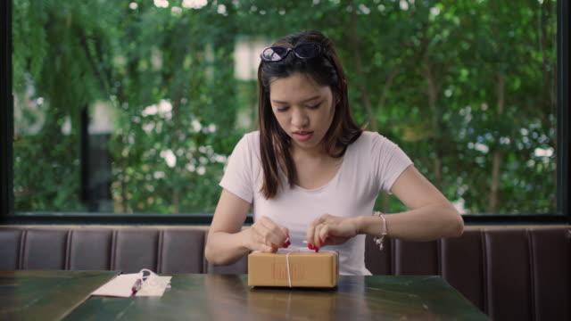 vídeos de stock, filmes e b-roll de jovem embrulhou uma caixa de presente - trabalhadora de colarinho branco