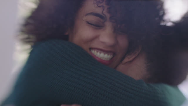 CU SLO MO. Young woman wraps arms around boyfriend with a hug as he lifts her up in modern coffee shop.