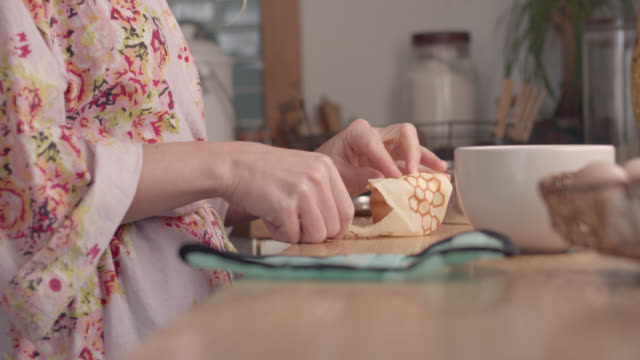 cu young woman wraps muffin in reusable food wrap on kitchen counter - つつむ点の映像素材/bロール
