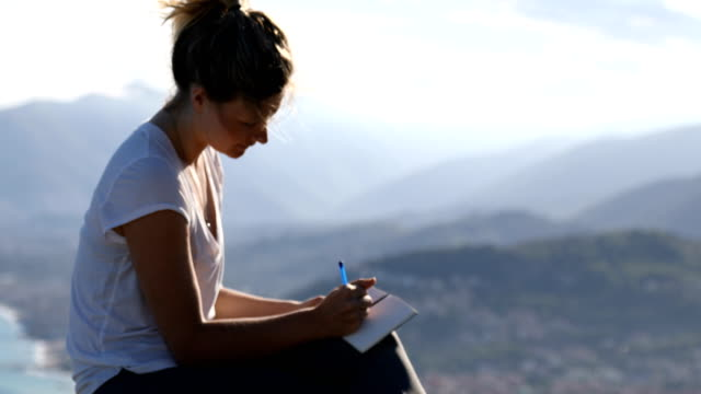 young woman writes in notebook above coastal mountains - diary stock videos & royalty-free footage