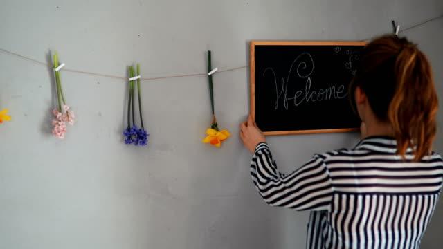 Eine junge Frau schreiben, Willkommen an Bord und setzen Dekoration an der Wand