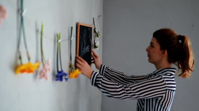 a young woman writing a welcome note on the board and putting decoration on the wall - dining room stock videos & royalty-free footage