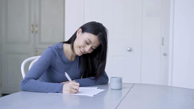 Jonge vrouw schrijven van een essay voor college en koffie drinken