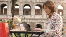 Young woman writing and working on her laptop computer sitting at the table outside in a bar in front of the Colosseum in Rome. Elegant beautiful dress and colorful shopping bags.
