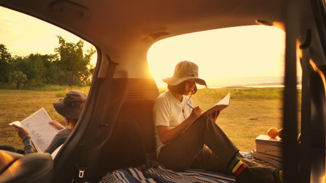 young woman writing book in the car at sunset - car interior stock videos & royalty-free footage