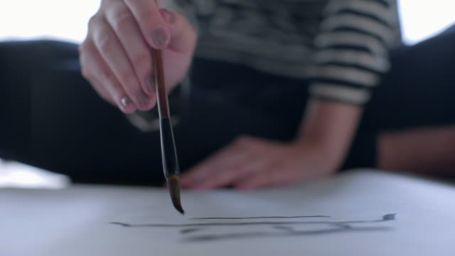 CU Young woman writing calligraphy with paint brush