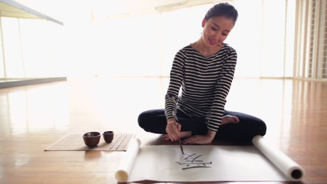 ms young woman writing chinese calligraphy artwork in  studio - chinese script stock videos & royalty-free footage
