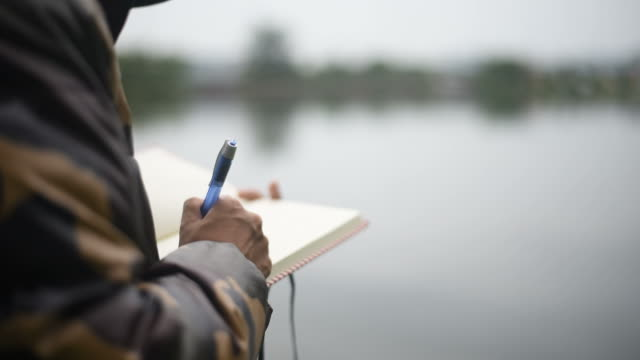 young woman writing in her diary book beside the lake. - diary stock videos & royalty-free footage