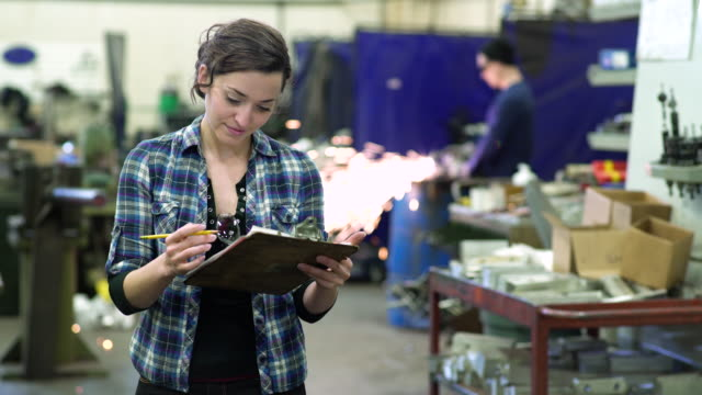Young woman writing on a clipboard in a factory