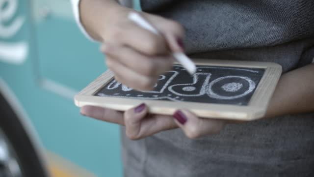 vídeos y material grabado en eventos de stock de cu young woman writing open on a sign - señal de abierto
