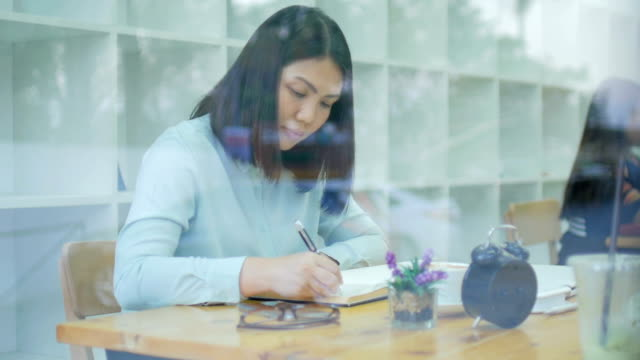 young woman writing take a note working at library - e learning stock videos & royalty-free footage