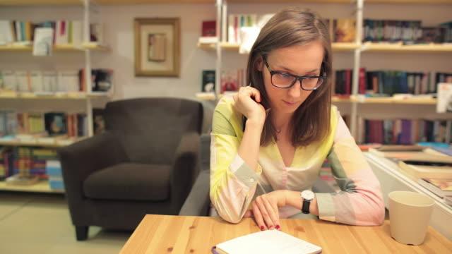 Junge Frau schreiben Notizen Während sie trinkt Kaffee.