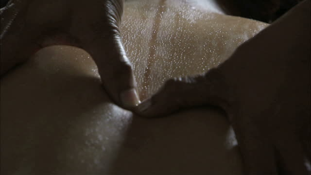 CU TU TD Young woman's back massage with oil by hand / India