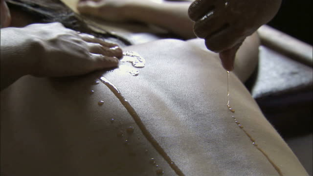CU PAN Young woman's back massage with oil by hand / India