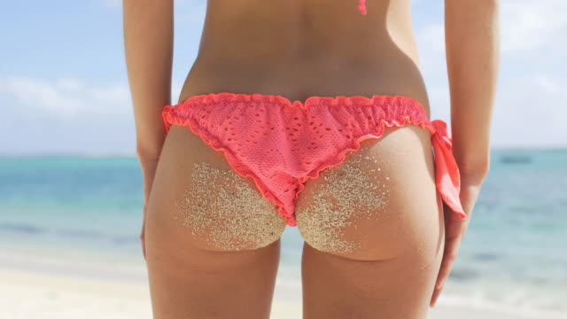 Young woman's buttocks in bikini covered in sand at seaside