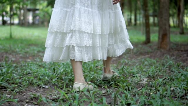 vídeos y material grabado en eventos de stock de pies de mujer joven en pasto - vestido