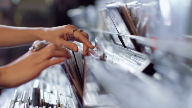 cu a young woman's fingers flick through a rack of vintage records - picking stock videos & royalty-free footage