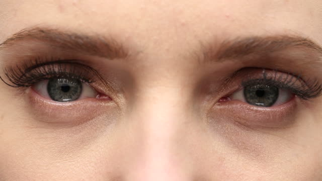 CU of young woman's green eyes as she rubs one of them.