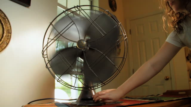 slo mo cu young woman's hand turning on fan / madison, florida, usa - ventilator stock-videos und b-roll-filmmaterial