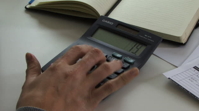 Young woman's hand using calculator, UK