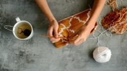 young womans hands crochet hook