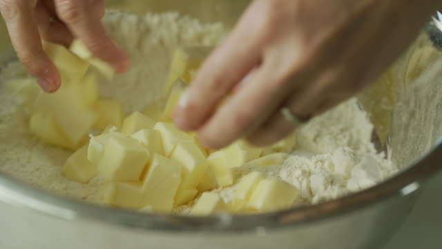 a young woman's hands cut butter into small pieces with a large kitchen knife on a wooden cutting board and then pick up the butter and sprinkle it over flour in a metal mixing bowl - pastry dough stock videos & royalty-free footage