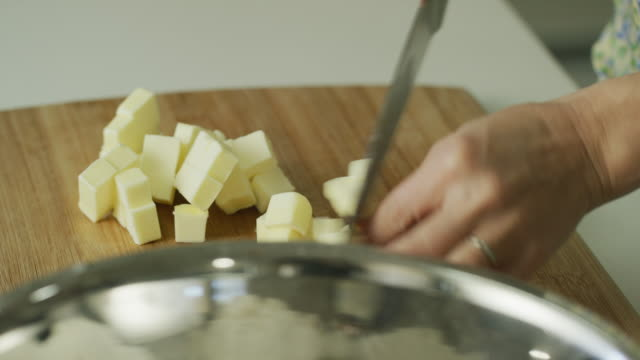 a young woman's hands cut butter into small pieces with a large kitchen knife on a wooden cutting board, pick up the butter, and sprinkle it over flour in a metal mixing bowl - dough stock videos & royalty-free footage