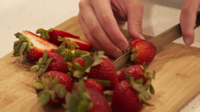 young woman's hands cutting fresh strawberries to decorate a cake - chopping board stock videos & royalty-free footage