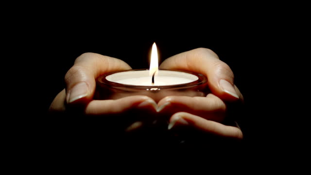 young woman's hands holding a burning candle - mourner stock videos & royalty-free footage