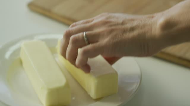 en ung kvinnas händer flytta en pinne av smör från en platta till en trä skärbräda på ett vitt bord bredvid en kökskniv - smör bildbanksvideor och videomaterial från bakom kulisserna