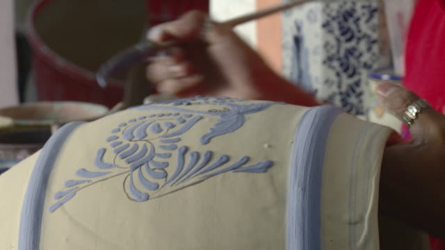 cu young woman's hands painting talavera pottery / puebla, mexico - craft product stock videos and b-roll footage