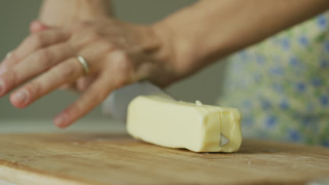 a young woman's hands place a stick of butter on to a wooden cutting board and uses a large kitchen knife to cut into it in a cozy indoor kitchen - butter stock videos & royalty-free footage