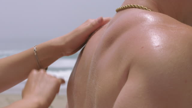 young woman's hands rub sunscreen on young man's back at the beach 4k - vesper stock stock videos & royalty-free footage