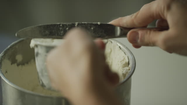 a young woman's hands use a metal measuring cup to scoop flour from a canister and then use a kitchen knife to remove excess from the top before pouring it into a mixing bowl - flour stock videos & royalty-free footage