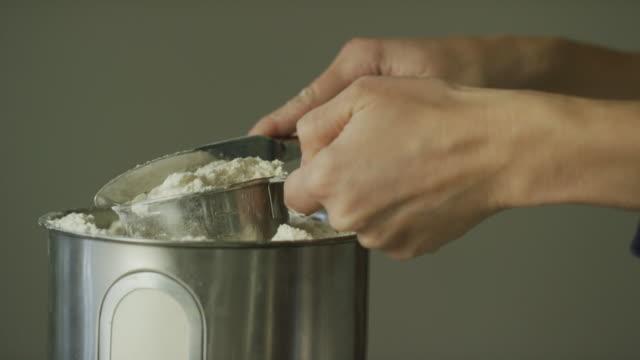 若い女性の手は小さなかんから小麦粉をスクープし、上部から過剰を削除する包丁を使用して計量カップ金属を使用します。 - 部分点の映像素材/bロール