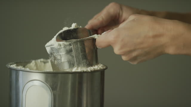 a young woman's hands use a metal measuring cup to scoop flour from a canister and then use a kitchen knife to remove excess from the top - measuring stock videos & royalty-free footage