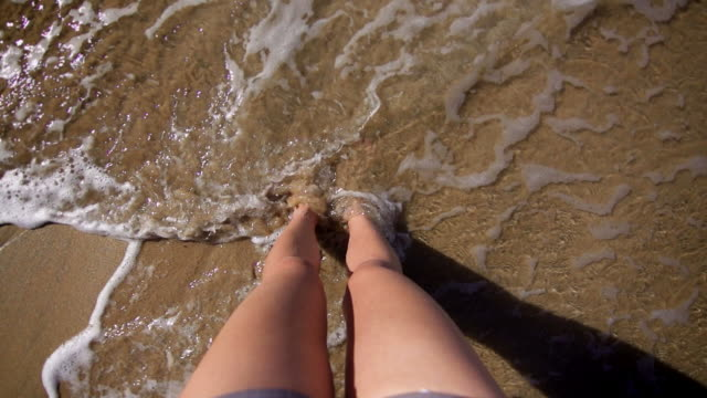 Young woman's legs on a sandy beach, wave washing up
