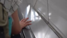 young woman's right hand holding on the escalator handrail