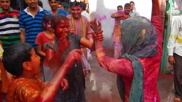 stockvideo's en b-roll-footage met young women and a kid dancing while water and coloured is thrown at them / religious festivities and celebrations inside the temple complex in... - holi phagwa